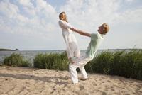 Woman balancing on friend's knee at beach against sky 11016033571| 写真素材・ストックフォト・画像・イラスト素材|アマナイメージズ