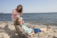 Smiling woman feeding cherry to friend while relaxing at beach 11016033573| 写真素材・ストックフォト・画像・イラスト素材|アマナイメージズ