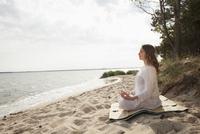 Woman meditating on sea shore at beach against sky 11016033574| 写真素材・ストックフォト・画像・イラスト素材|アマナイメージズ