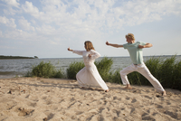 Friends practicing yoga on sea shore at beach against sky 11016033575| 写真素材・ストックフォト・画像・イラスト素材|アマナイメージズ