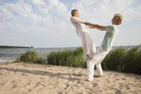 Friend balancing on man's knee at beach against sky 11016033583| 写真素材・ストックフォト・画像・イラスト素材|アマナイメージズ