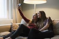 Siblings taking selfie through mobile phone in living room 11016033601| 写真素材・ストックフォト・画像・イラスト素材|アマナイメージズ