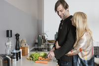 Affectionate mature couple cooking food together in kitchen 11016033602| 写真素材・ストックフォト・画像・イラスト素材|アマナイメージズ