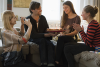 Happy woman looking at family with birthday cake in living room 11016033603| 写真素材・ストックフォト・画像・イラスト素材|アマナイメージズ