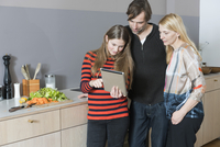 Parents with daughter cooking while using digital tablet in kitchen 11016033610| 写真素材・ストックフォト・画像・イラスト素材|アマナイメージズ