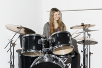 Young woman smiling while playing drums 11016033616| 写真素材・ストックフォト・画像・イラスト素材|アマナイメージズ