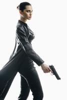 Female spy with gun walking against white background 11016033642| 写真素材・ストックフォト・画像・イラスト素材|アマナイメージズ