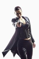 Portrait of female spy aiming gun while standing against white background 11016033645| 写真素材・ストックフォト・画像・イラスト素材|アマナイメージズ