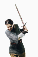 Angry woman wearing chain mail holding sword against white background