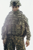 Portrait of army soldier carrying rifle standing against white background