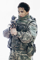 Angry army soldier aiming rifle while standing against white background