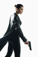 Furious spy holding gun walking against white background 11016033651| 写真素材・ストックフォト・画像・イラスト素材|アマナイメージズ