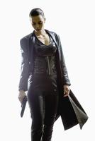 Female spy holding gun while walking against white background 11016033659| 写真素材・ストックフォト・画像・イラスト素材|アマナイメージズ
