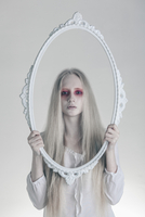 Portrait of woman with spooky red eyes holding picture frame against white background 11016033660| 写真素材・ストックフォト・画像・イラスト素材|アマナイメージズ