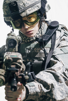 Army soldier wearing goggles aiming rifle while standing against white background