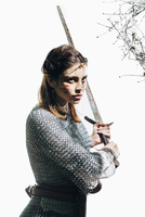 Angry female warrior wearing chain mail holding sword against white background 11016033663| 写真素材・ストックフォト・画像・イラスト素材|アマナイメージズ