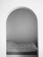 Bed and room seen through an arch