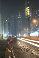 Light trails on street against illuminated buildings in city at night 11016033694| 写真素材・ストックフォト・画像・イラスト素材|アマナイメージズ