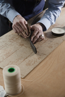 High angle view of man rubbing leather belt on wooden table