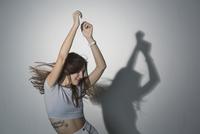 Beautiful woman dancing against gray background 11016033717| 写真素材・ストックフォト・画像・イラスト素材|アマナイメージズ