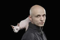 Portrait of bald man carrying Sphynx hairless cat on shoulder against black background