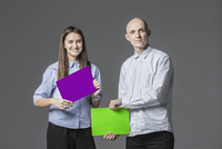 Portrait of business people holding placards against gray background 11016033730| 写真素材・ストックフォト・画像・イラスト素材|アマナイメージズ