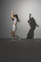 Full length of woman dancing against gray background 11016033747| 写真素材・ストックフォト・画像・イラスト素材|アマナイメージズ