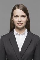 Portrait of confident businesswoman against gray background 11016033753| 写真素材・ストックフォト・画像・イラスト素材|アマナイメージズ