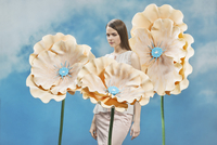 Thoughtful beautiful woman standing amidst flower props against sky 11016033754| 写真素材・ストックフォト・画像・イラスト素材|アマナイメージズ