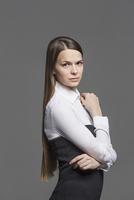Portrait of confident woman standing against gray background 11016033756| 写真素材・ストックフォト・画像・イラスト素材|アマナイメージズ
