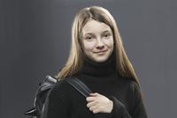 Portrait of smiling student standing against gray background 11016033762| 写真素材・ストックフォト・画像・イラスト素材|アマナイメージズ
