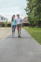 Man holding skateboard walking with girlfriend on footpath by trees at park