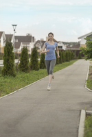 Young woman jogging on footpath by topiary in residential district