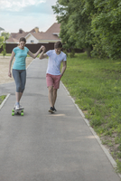 Man assisting girlfriend in riding skateboard on footpath at park