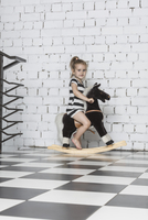 Portrait of girl playing on rocking horse against wall at home