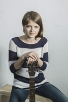 Portrait of smiling teenager holding guitar while sitting on bench against wall