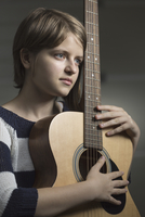 Thoughtful teenager holding guitar against wall