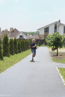 Boy skateboarding on road amidst trees against houses in town