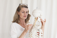 Confident female doctor looking at skeleton while standing in clinic 11016033929| 写真素材・ストックフォト・画像・イラスト素材|アマナイメージズ