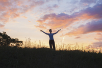 Woman standing with arms outstretched on grassy field against sky during sunset 11016033931| 写真素材・ストックフォト・画像・イラスト素材|アマナイメージズ