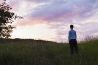 Rear view of woman standing on grassy field against sky during sunset 11016033938| 写真素材・ストックフォト・画像・イラスト素材|アマナイメージズ
