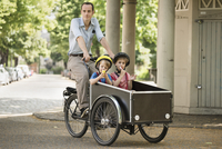 Father with boys riding bicycle with cart on street