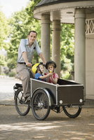 Smiling father riding bicycle while boys sitting in cart on street