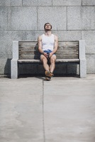 Tired young man sitting on wooden bench against wall