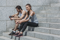 Happy friends in sportswear sitting on steps by wall