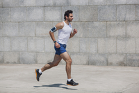 Determined sportsman jogging on sidewalk by wall