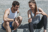 Cheerful woman showing smart phone to male friend while sitting on steps