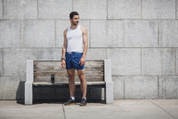 Serious sportsman standing by wooden bench on sidewalk against wall