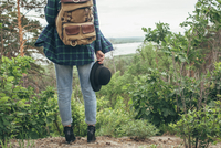 Low section of female backpacker holding hat while standing at forest 11016034025| 写真素材・ストックフォト・画像・イラスト素材|アマナイメージズ
