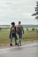 Couple walking on roadside by field against sky 11016034031  写真素材・ストックフォト・画像・イラスト素材 アマナイメージズ